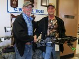 SJIHA President Larry Skinkle (L) presents bow to draw winner Terry Brason (R).