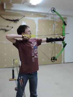 Caius Frolick shooting a compound bow.