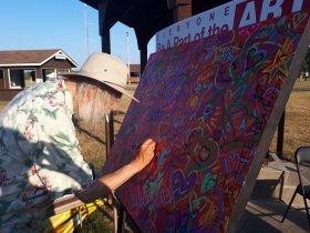 Local artist Doug Hook can't resist being part of the art project and signs his name.