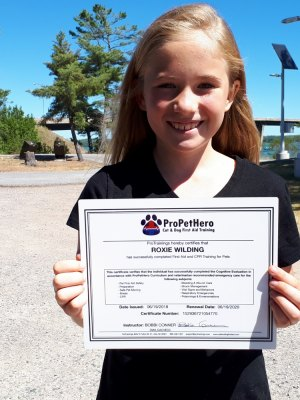 Roxie proudly displays her First Aid/CPR certificate.