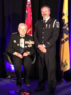 Derrick Bates (R) receives Exemplary Service Medal .