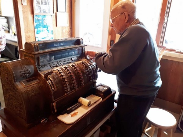 Harold working the old cash register still used for syrup sales at the Kent Bros camp. It came out of Jack Allen's store in Richards Landing which is now the LCBO.